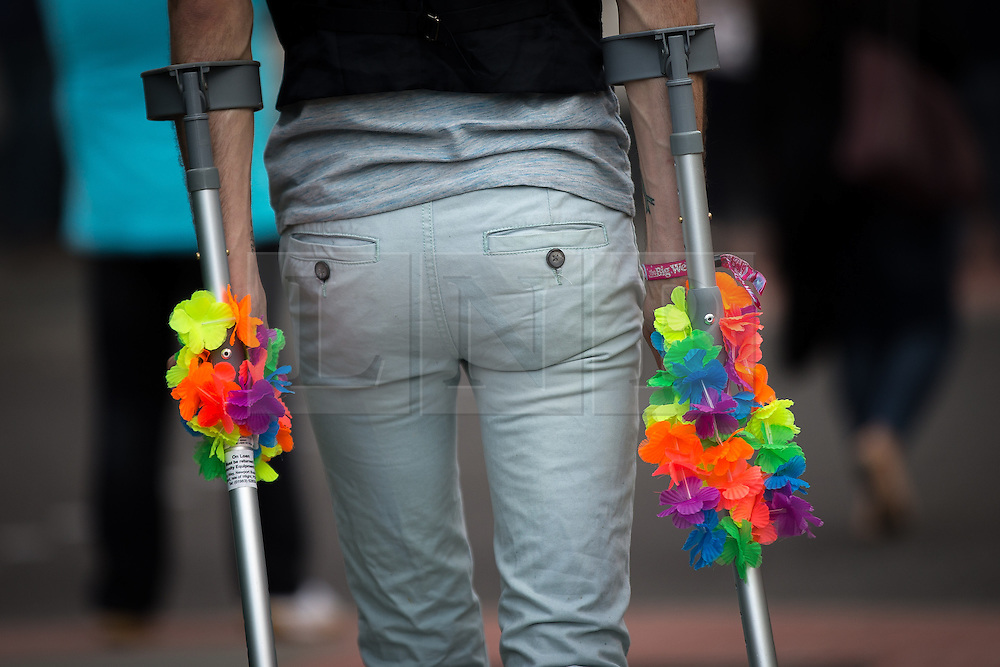 © Licensed to London News Pictures . 26/08/2016 . Manchester , UK . A man with rainbow garlands around his crutches in Manchcester's Gay Village for 2016 Manchester Gay Pride Big Weekend . Photo credit : Joel Goodman/LNP