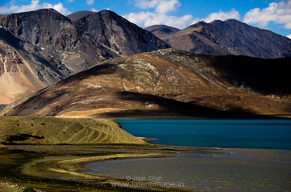 Pangong Tso. At the altitude of 14270 ft, it is one of the highest located lakes in the world. Out of 134 km, 60% of its total length is in Tibet, controlled by China. Landscapes by Jagjit Singh