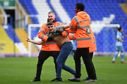 Stewards tackle a pitch invader during the EFL Sky Bet League 1 match between Coventry City and Doncaster Rovers at the Trillion Trophy Stadium, Birmingham, England on 28 September 2019.