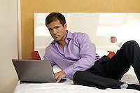 Portrait of young man using laptop on bed