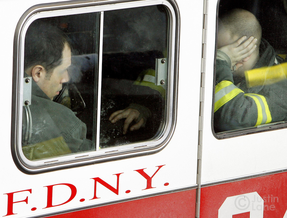 Two fire fighters sit in a fire truck outside of a house where 9 people were killed, 8 of them children, in a fire over night in the Bronx, New York on Thursday 08 March 2007.