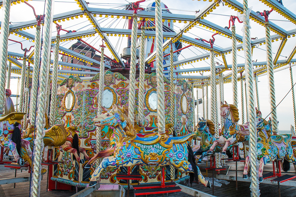 © Licensed to London News Pictures. 28/12/2015. Brighton, UK. The Carousel on Brighton pier currently undergoing repairs while People relax on Brighton beach as the weather turns increasingly warmer. Today December 28th 2015. Photo credit: Hugo Michiels/LNP