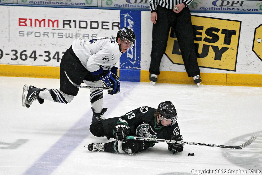 Roughriders' Tom Forgione (13) eyes the puck as he slides along the ice as the Force's Jonny Brodzinski (22) looks on during their game at the Cedar Rapids Ice Arena, 1100 Rockford Road SW in Cedar Rapids on Saturday evening, February 18, 2012. (Stephen Mally/Freelance)