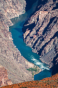 The Colorado River, seen from Hopi Point, in Grand Canyon National Park, Arizona, USA. Starting at least 5 to 17 million years ago, erosion by the Colorado River has exposed a column of distinctive rock layers, which date back nearly two billion years at the base of Grand Canyon. While the Colorado Plateau was uplifted by tectonic forces, the Colorado River and tributaries carved Grand Canyon over a mile deep (6000 feet), 277 miles  long and up to 18 miles wide.