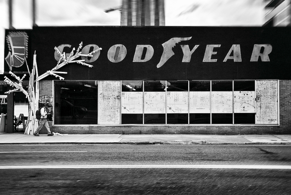 Construction worker walking down a sidewalk past an abandoned Goodyear building in downtown Charlotte, North Carolina.