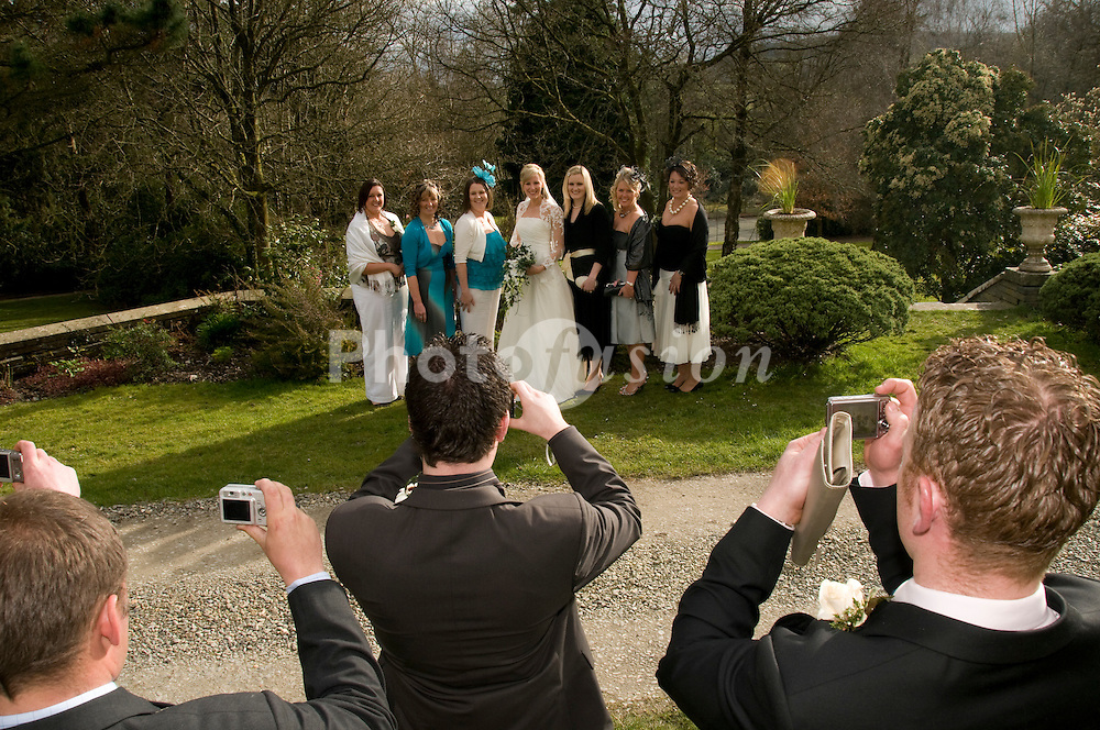 Men photographing their girlfriends with the bride at a wedding reception in west wales