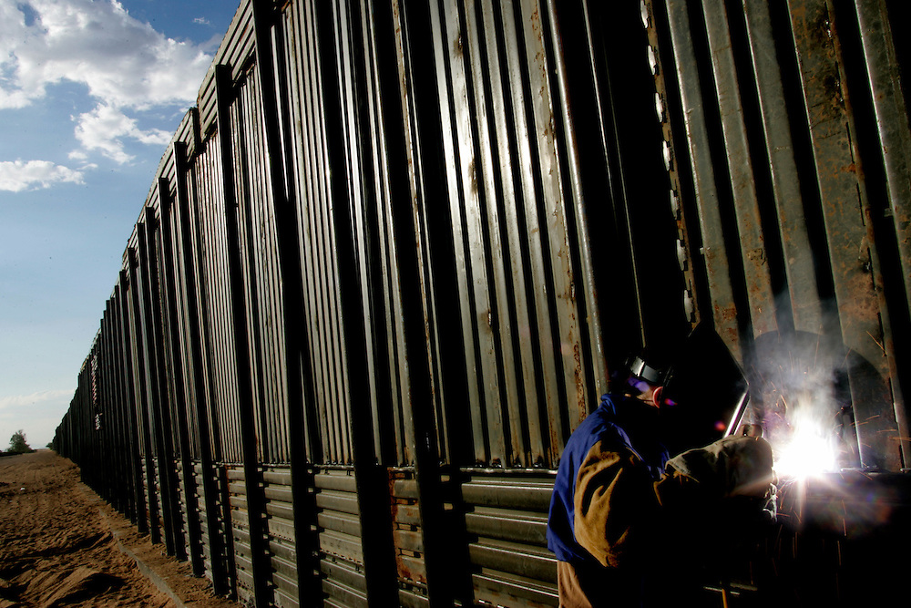 Sgt. David Cowley of the 115th Group of the Utah National Guard welds panelling on a newly constructed barrier fence along the US-Mexico border near San Luis, AZ on Wednesday, June 7, 2006.<br />