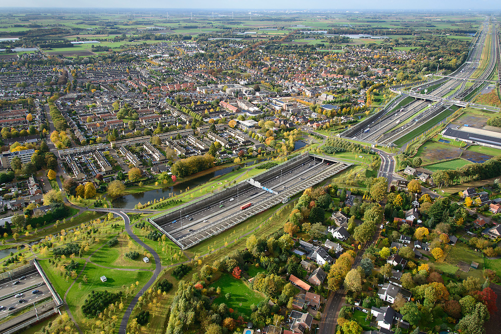 Nederland, Noord-Brabant, Gemeente Breda, 23-10-2013; Infrabundel, combinatie van autosnelweg A16 gebundeld met de spoorlijn van de HSL (re). Stadsduct Overbos in de voorgrond met Stadsduct Overbos daar achter. De bundel loopt in tunnelbakken, lokale wegen gaan over deze infrabundel heen, door middel van de zogenaamde stadsducten, gedeeltelijk ingericht als stadspark. Combination of motorway A16 and the HST railroad, crossed by local roads by means of *urban ducts*, partly designed as public parks.<br /> luchtfoto (toeslag op standard tarieven);<br /> aerial photo (additional fee required);<br /> copyright foto/photo Siebe Swart