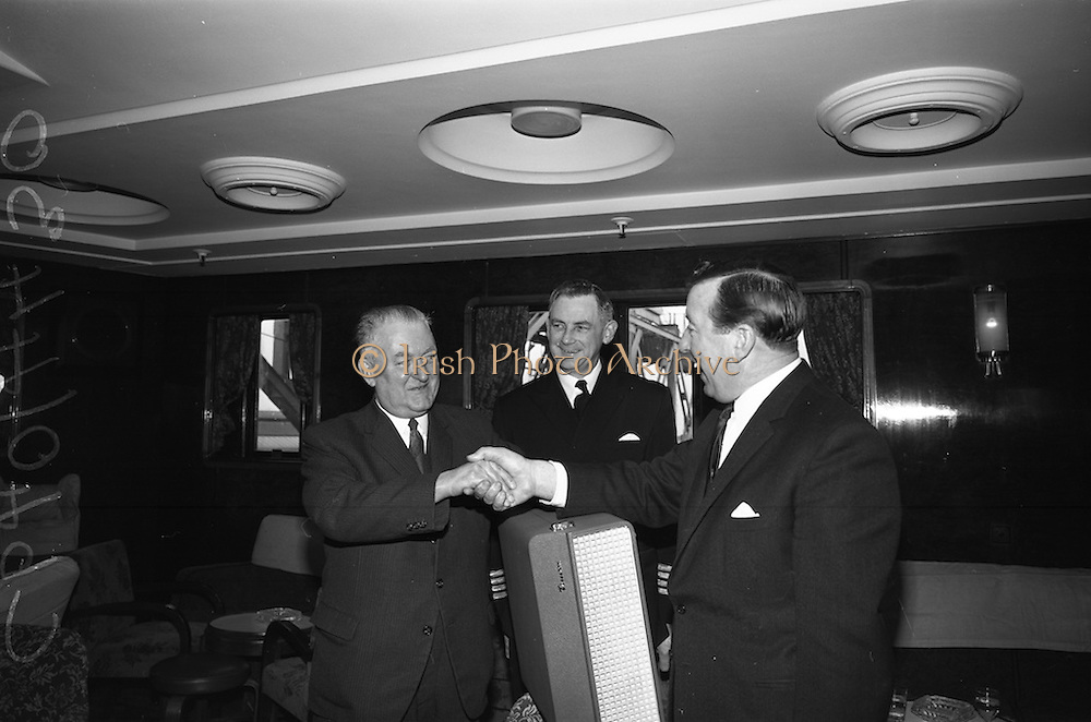 """06/04/1966<br /> 04/06/1966<br /> 06 April 1966<br /> Captain John Williams retires as Master of B & I ship the M.V. """"Munster"""". Captain Williams was presented with a tape recorder by the Masters, Officers and staff of all the B & I ships. Picture shows Captain Gerald Barry, (right)Master of the M.V. """"Leinster"""" making the presentation to Captain Williams. Captain Matthew Hollywood (centre) was the new Master of the M.V. """"Munster""""."""