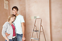 Couple standing embracing in unrenovated room portrait