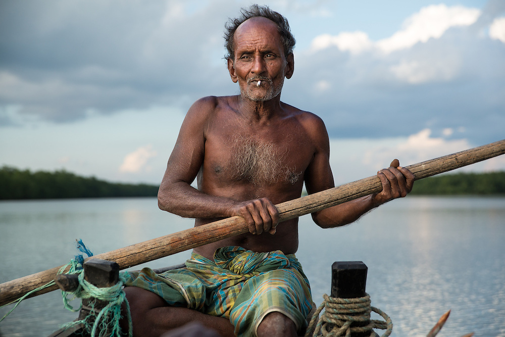 Philip Mondal, a small-scale fisherman deep in the Sundarbans - the world's largest mangrove forest. He makes 7 to 10 day fishing trips here with his son and nephew, living on their small slender boat and sailing and paddling about 125 km from their home village. Before he wasn't a fisherman but a farmer. Like many farmers in the region, he lost his low-lying land to the sea - climate change causing sea level rise and increasingly intense storms, meant that his land was frequently flooded by the sea and became too salty to cultivate. So he and his family, like so many other farmers in the area, turned to fishing to survive. In the Sundarbans traditional fishermen must contend with tigers, crocodiles and storms. But by far the greatest threat to their lives are the dacoit: Bandits who live in the forest and who will kidnap fishermen, holding them hostage until their families pay ransom by mobile phone payments.