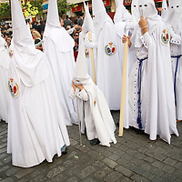 A young penitent leaning on a stick during a Holy Week procession, Seville, Spain