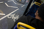 London commuter wearing earrings rides on a bus with stencilled cycle route stencil outside of window.