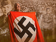 World War II veteran George Mills,93, holds a Nazi flag he liberated from a public building in a town on the Luxembourg-German border as his E Company, 109th Infantry, 28th Division advanced in the winter of 1944 just before the Battle of the Bulge.  Mills was a sergeant and was captured three days into the Battle of the Bulge.