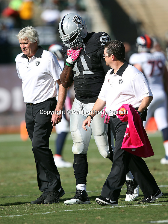 Oakland Raiders defensive end Justin Tuck (91) gets help walking off the field with an apparent injury after tackling Denver Broncos running back C.J. Anderson (22) on a fourth quarter play during the 2015 NFL week 5 regular season football game against the Denver Broncos on Sunday, Oct. 11, 2015 in Oakland, Calif. The Broncos won the game 16-10. (©Paul Anthony Spinelli)