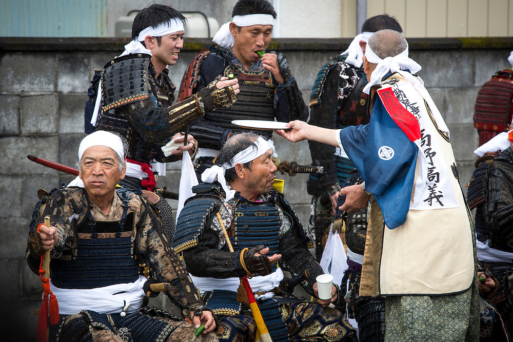 """MINAMISOMA, JAPAN - JULY 24 :  A samurai men eats as they prepare for the battle race during the """"Hon Matsuri"""", Soma Nomaoi festival at Hibarigahara field on Sunday, July 24, 2016 in Minamisoma, Fukushima Prefecture, Japan. """"Soma-Nomaoi"""" is a three day traditional festival that recreates a samurai battle scene from more than 1,000 years ago. The festival has gathered more than thousands visitors as Fukushima still continues to recovery from the 2011 nuclear disaster, the samurai warriors battles for recovery of the area. (Photo: Richard Atrero de Guzman/NURPhoto)"""
