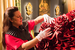 "Sotheby's, London, January 14th 2016. Paper artist ZOE BRADLEY exhibits spectacular paper sculptures inspired by the fashion in old master paintings. Her astonishing works are exhibited alongside 460 royal and aristocratic heirlooms  that will appear in Sotheby's ""Of Royal and Noble Descent"" auction to be held between 14th and 18th January. PICTURED: Paper sculptor Zoe Bradley puts the finishing touches to her installation , a monumental red ruffle gown, made up of 5,940 ruffles of paper. ///FOR LICENCING CONTACT: paul@pauldaveycreative.co.uk TEL:+44 (0) 7966 016 296 or +44 (0) 20 8969 6875. ©2015 Paul R Davey. All rights reserved."