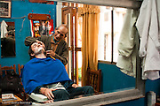 An American getting an old-fashioned shave in a barber shop in Cusco, Peru.