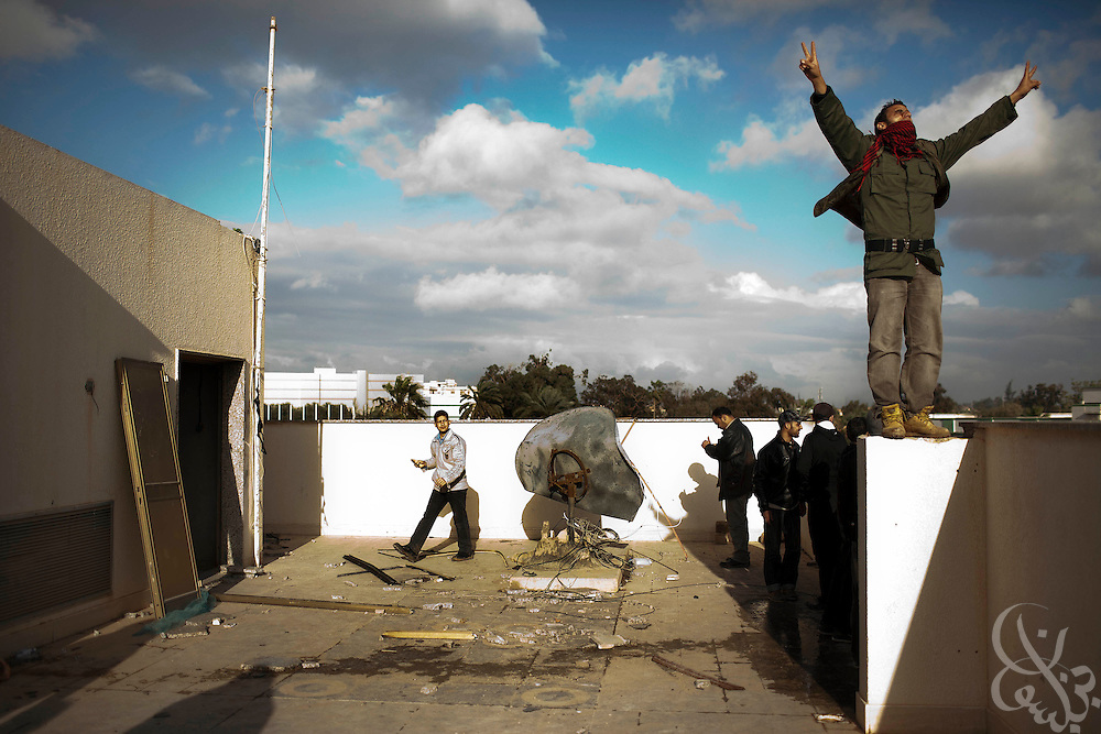A Libyan man gestures in celebration atop a house belonging to Libyan leader Col. Muammar el-Qaddafi inside the abandoned and looted Katiba el-Fedeel Boummar military base in Benghazi Libya February 24, 2011. A tightening circle of rebels threatened the capital, Tripoli, on Thursday, as government forces try to fend off an uprising against the 40-year rule of Col. Muammar el-Qaddafi..Slug: Libya.Credit: Scott Nelson for the New York Times