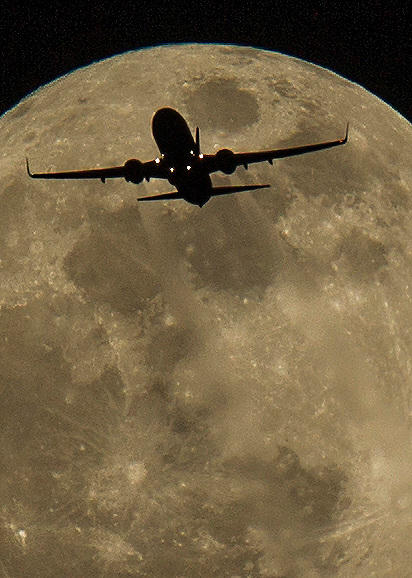 An airplane approaches Los Angeles International Airport and flies past the first full moon of the year on Sunday, January 4, 2015 in Los Angeles, California.  (Photo by Ringo Chiu/PHOTOFORMULA.com)