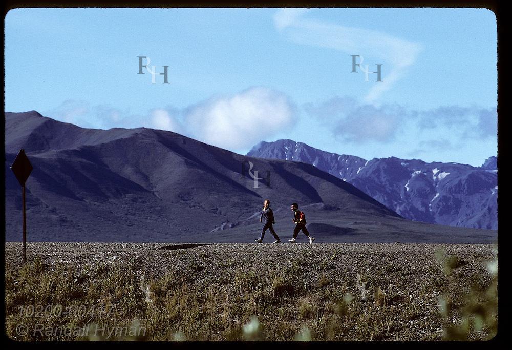 Two boys walk atop road embankment against backdrop of distant Alaska Range; Denali National Park. Alaska