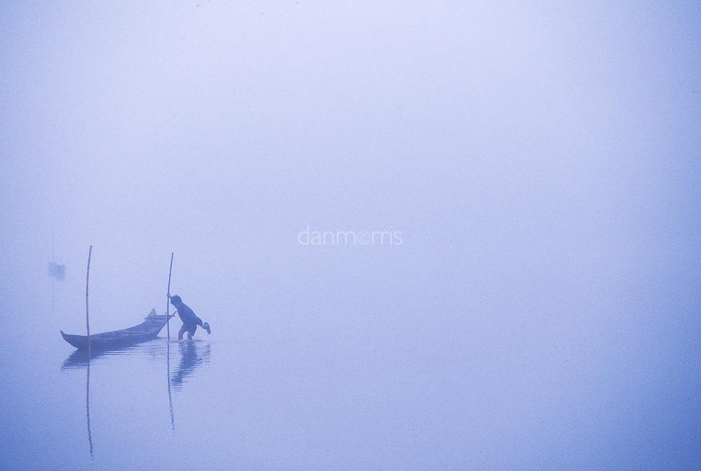 Boy prepares fishing boat in early morning mist, Ban Pak Ou, Luang Phrabang, Laos