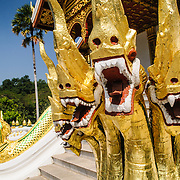 Golden naga (King Cobras) decorate teh stairs of Haw Pha Bang (or Palace Chapel) at the Royal Palace Museum in Luang Prabang, Laos. The chapel sits at the northeastern corner of the grounds. Construction started in 1963.