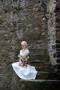 a lady in a white period dress is sitting on old stone steps