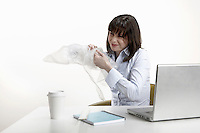 Woman sitting at desk playing with bubble wrap