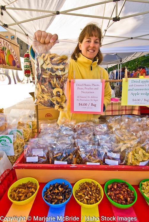 Woman selling dried fruit at Farmers Market in downtown, Boise, Idaho.   Model Release