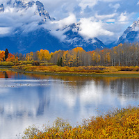 Panorama photo of the Grand Teton mountains with the Snake River and Oxbow Bends in the foreground. Fall colors