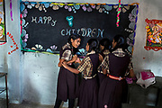 On Children's Day 2014, November 14, Poonam's sister Jyoti, 13, is arguing with a classmate over a piece of chalk, while playing around near a blackboard, inside a room of the cozy, private schooll the sisters regularly attend since 2011, located by their newly built home in Oriya Basti, one of the water-contaminated colonies in Bhopal, central India, near the abandoned Union Carbide (now DOW Chemical) industrial complex, site of the infamous '1984 Gas Disaster'.