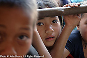 A student at The Ban Namha Primary School in Ban Namha, Laos, looks through the arms of her classmates. The school is attended by 250 children who range in age from 5 to 12, and is served by 5 faculty members. This facility was constructed by the European Union (EU) in 1998, but lacks basic learning supplies such as books, paper and recreational equipment.