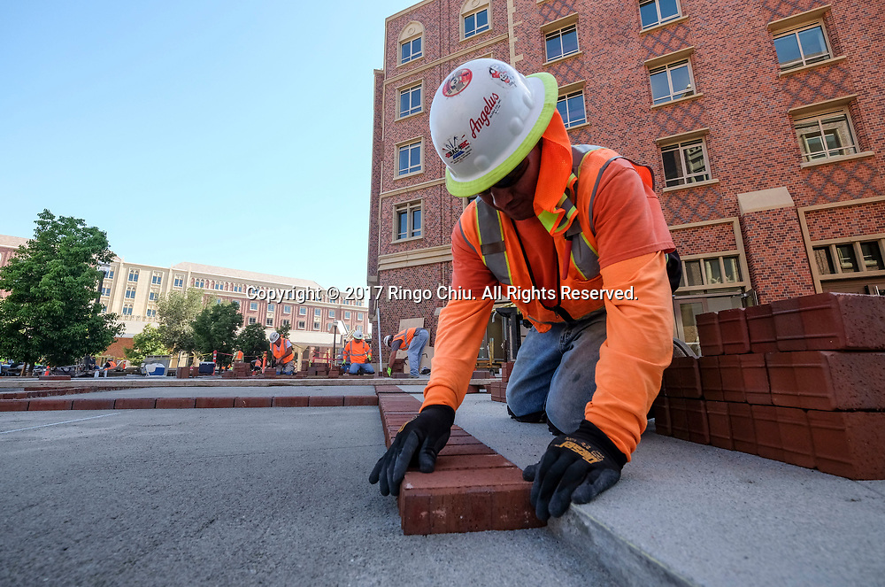 A worker installs the bricks in USC's University Village. USC's $700 million shopping and residential complex is nearly complete and more than a dozen retailers (Trader Joe's, Target, Starbucks, etc.) are set to open in August. (Photo by Ringo Chiu)<br /> <br /> Usage Notes: This content is intended for editorial use only. For other uses, additional clearances may be required.