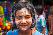 13 APRIL 2013 - BANGKOK, THAILAND: A woman in Bangkok with paste on her face during Songkran celebrations in the Thai capital. The paste is a part of the traditional celebration of Songkran and is thought to ward off evil. Songkran is celebrated in Thailand as the traditional New Year's Day from 13 to 16 April. The date of the festival was originally set by astrological calculation, but it is now fixed. If the days fall on a weekend, the missed days are taken on the weekdays immediately following. Songkran is in the hottest time of the year in Thailand, at the end of the dry season and provides an excuse for people to cool off in friendly water fights that take place throughout the country. Songkran has been a national holiday since 1940, when Thailand moved the first day of the year to January 1.    PHOTO BY JACK KURTZ