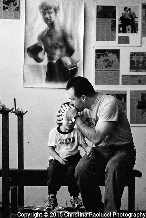 Rick Mueller kisses his son four-year-old son Christian  and entertains him while  Lorie  participates in a Saturday morning Bible study program at the Fourth Street Boxing Gym before boxing practice.