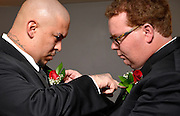 Soon to be brothers-in-law make the final adjustment of each others boutonniere prior to the wedding ceremony, Arizona, USA.