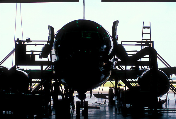 Airplane sitting in the hangar for maintenance by crew
