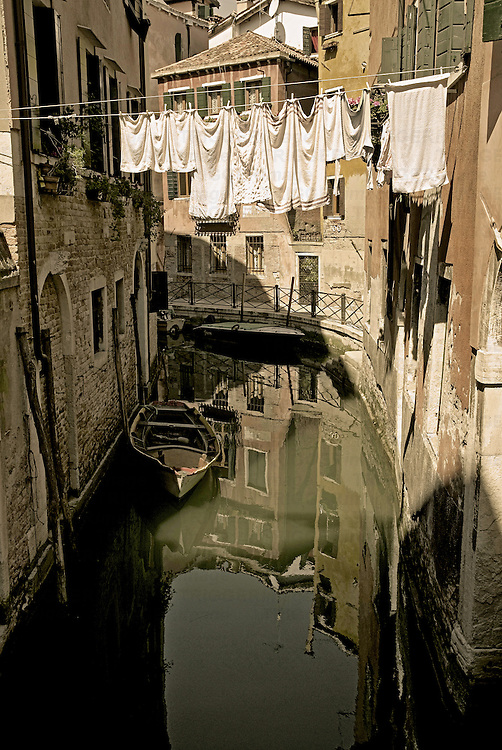 Laundry drying on a clothesline, hanging over a canal in Venice, Italy.