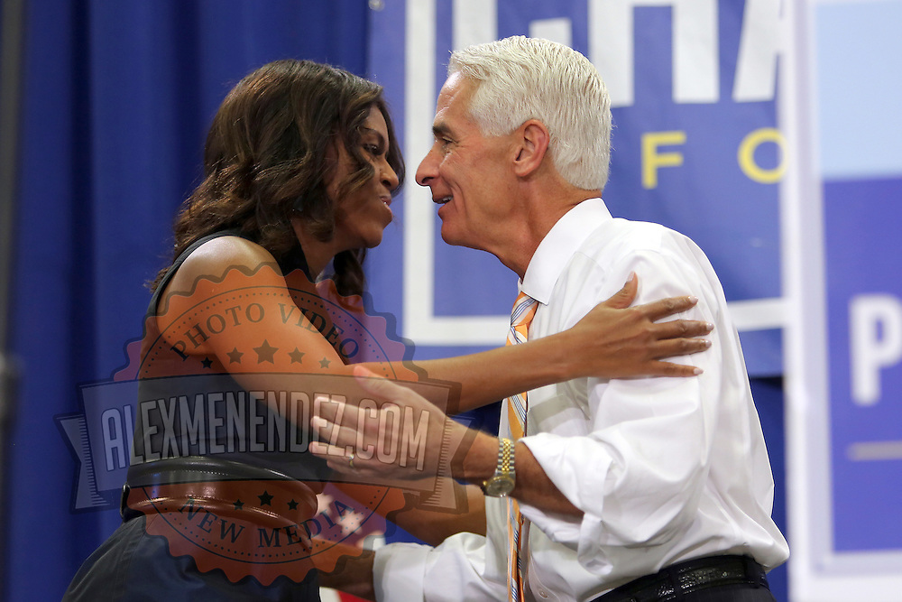 """First Lady Michelle Obama hugs Charlie Crist prior to his grassroots """"Commit to Vote"""" rally at the Barnett Park Gymnasium in Orlando, Florida on Friday, Nov. 17, 2014. (AP Photo/Alex Menendez)"""