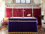 Altar with candles and crucifix inside church at Bradenstoke, Wiltshire, England, UK