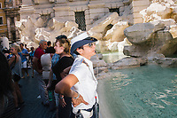 """ROME, ITALY - 20 JUNE 2017: A Roman policewoman, entrusted to protect the Fountain of Trevi, blows her whistle at tourists that were sitting on the edge of the fountain in Rome, Italy, on June 20th 2017.<br /> <br /> The warm weather has brought a menacing whiff of tourists behaving badly in Rome. On April 12, a man went skinny-dipping in the Trevi fountain resulting in a viral web video and a 500 euro fine.<br /> <br /> Virginia Raggi, the mayor of Rome and a national figurehead of the anti-establishment Five Star Movement,  issued an ordinance involving harsher fines for eating, drinking or sitting on the fountains, for washing animals or clothes in the fountain water or for throwing anything other than coins into the water of the Trevi Fountain, Bernini's Four Fountains and 35 other city fountains of artistic or historic significance around the city.  """"It is unacceptable that someone use them to go swimming or clean themselves, it's an historic patrimony that we must safeguard,"""" Ms. Raggi said."""
