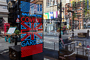 As the number of people dying with Covid-19 in hospitals in England rises by another 665 to 16,272, and the UK experiences further lockdown by the UK government due to the Coronavirus pandemic, a security guard keeps watch over deserted streets, businesses and retailers including footwear brand Skechers on the corner of in Floral and James Streets in Covent Garden suffer further economic losses after forced closure, on 22nd April 2020, in London, England.