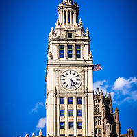Photo of the Chicago Wrigley building clock and top section. The Wrigley Building is a Chicago skyscraper on Michigan Avenue and was built in 1920 by the Wrigley gum company. Photo is vertical and high resolution.