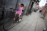 Yuanjing, a typical Hutong (old style district). Little girl on bicycle.