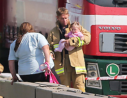 A firefighter with a baby at the scene of the multi car pile up on the A249 Isle of Sheppey  bridge in Kent, Thursday, 5th September 2013. Picture by Stephen Lock / i-Images