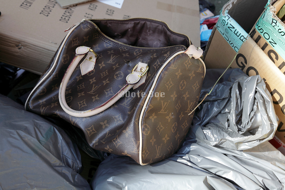 a broken Louis Vuitton handbag among street garbage