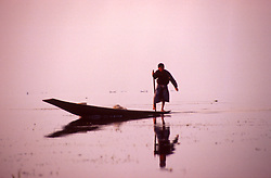 BURMA SHAN STATE INLE LAKE MAR95 - An Intha fisherman slowly moves his boat on Inle Lake. The Inle Lake is the only place in the world where fishermen row with one arm and one leg, thus leaving the other arm for reeling off the nets while moving. .. jre/Photo by Jiri Rezac. . © Jiri Rezac 1995. . Contact: +44 (0) 7050 110 417. Mobile: +44 (0) 7801 337 683. Office: +44 (0) 20 8968 9635. . Email: jiri@jirirezac.com. Web: www.jirirezac.com