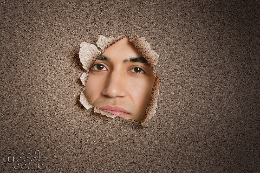 Portrait of a young Indian man peeking from ripped paper hole