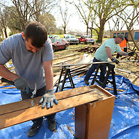 Thomas Wells | BUY at PHOTOS.DJOURNAL.COM<br /> Randy Parker, left, and Justin Popowich pull nails from wood planks as they help disassemble a home in East Tupelo that was once lived in by Elvis Presley.